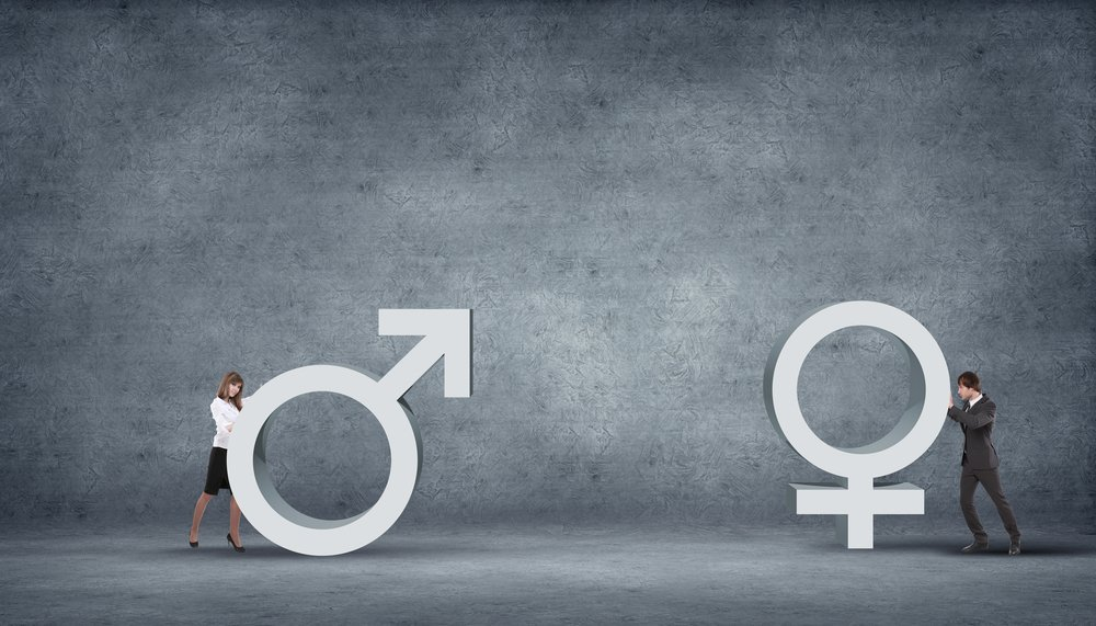 Image displays woman and man pushing gender emblems towards each other to represent gender diversity in tech