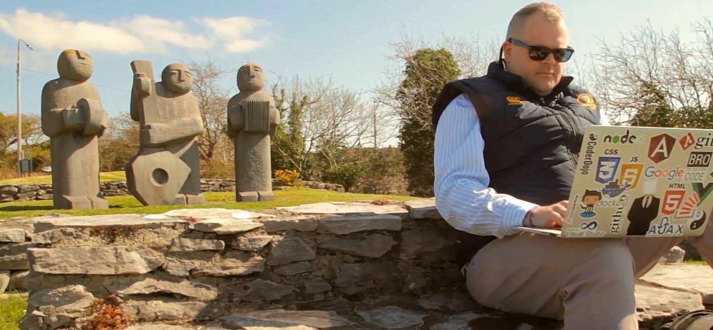Image shows Pierce O'Neill who career changed from sales to software development working on his laptop outside with three statues in the background.